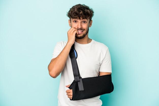 Młody arab ze złamaną ręką na białym tle na niebieskim tle gryzie paznokcie, nerwowy i bardzo niespokojny.