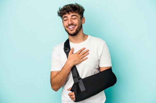 Młody arab ze złamaną ręką na białym tle na niebieskim tle śmieje się głośno trzymając rękę na klatce piersiowej.