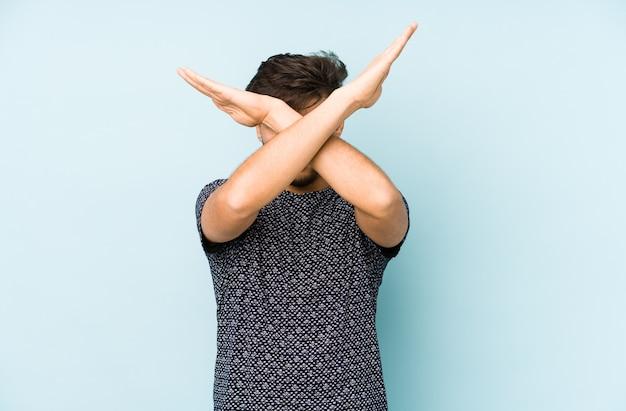 Młody arabian człowiek na niebiesko trzymając dwie skrzyżowane ręce, koncepcja odmowy.