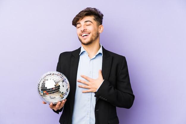 Młody arabian człowiek trzymający imprezową piłkę na białym tle śmieje się głośno, trzymając rękę na piersi.