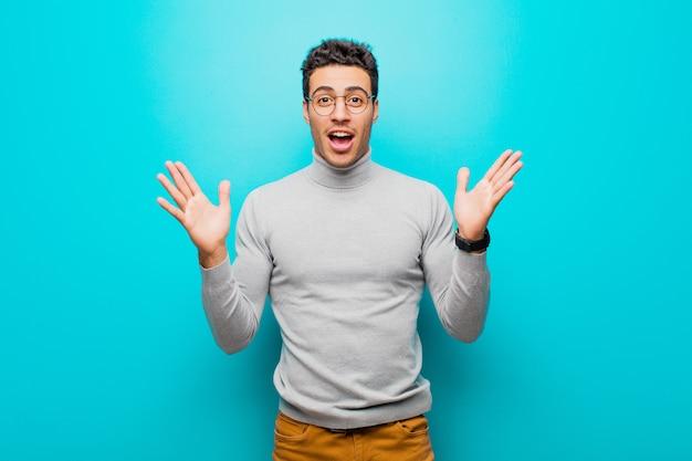 Młody arabian czuje się szczęśliwy, podekscytowany, zaskoczony lub zszokowany, uśmiechnięty i zdziwiony czymś niewiarygodnym na płaskiej ścianie
