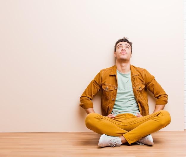 Młody arabian czuje się zdezorientowany lub pełny lub wątpliwości i pytania, zastanawia się, z rękami na biodrach, widok z tyłu siedzi na podłodze