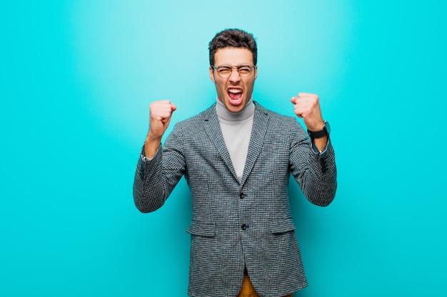 Młody arabian krzyczy agresywnie z gniewnym wyrazem twarzy lub zaciśniętymi pięściami, świętując sukces na niebieskiej ścianie