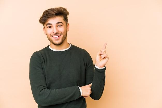 Młody arabian mężczyzna na białym tle na beżowym tle uśmiechnięty radośnie, wskazując palcem wskazującym z dala.