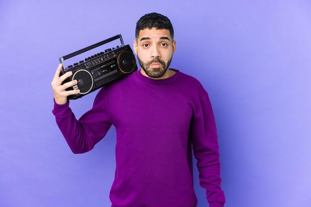 Młody arabian mężczyzna trzyma kasetę radiową na białym tle młody mężczyzna arabski słuchania muzyki wzrusza ramionami i otwarte oczy zdezorientowany.