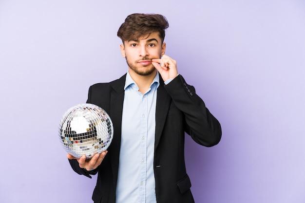 Młody arabian mężczyzna trzyma piłkę na białym tle z palcami na ustach, trzymając w tajemnicy.