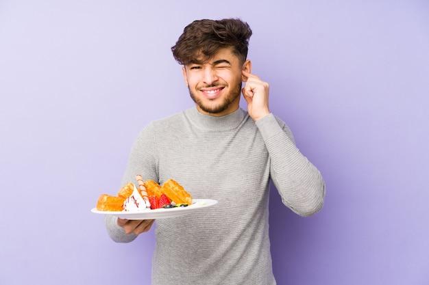 Młody arabian mężczyzna trzyma wafel na białym tle obejmujące uszy rękami.