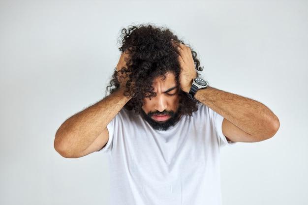 Młody arabianin z długimi włosami boli go głowa, cierpi na migrenę