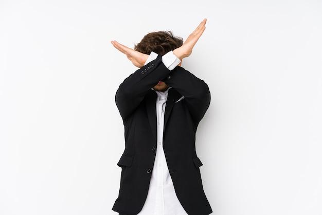 Młody arabski biznesmen na białym tle trzymając dwie skrzyżowane ręce, koncepcja odmowy.