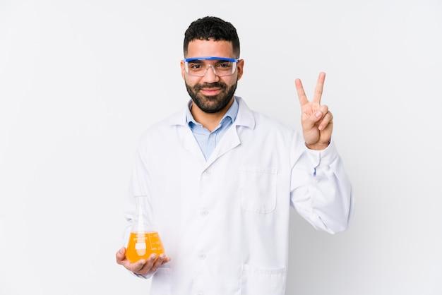 Młody arabski chemiczny mężczyzna odizolowywał pokazywać numer dwa z palcami.