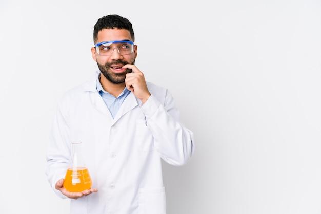 Młody arabski chemiczny mężczyzna odizolowywał zrelaksowanego główkowanie o coś patrzeje odbitkową przestrzeń.