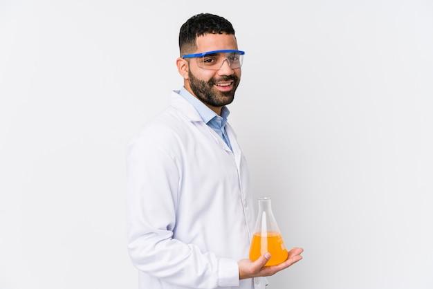 Młody arabski chemik na białym tle wygląda na bok uśmiechnięty, wesoły i przyjemny.