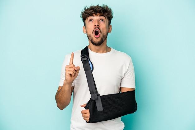 Młody arabski człowiek ze złamaną ręką na białym tle na niebieskim tle, wskazując do góry z otwartymi ustami.