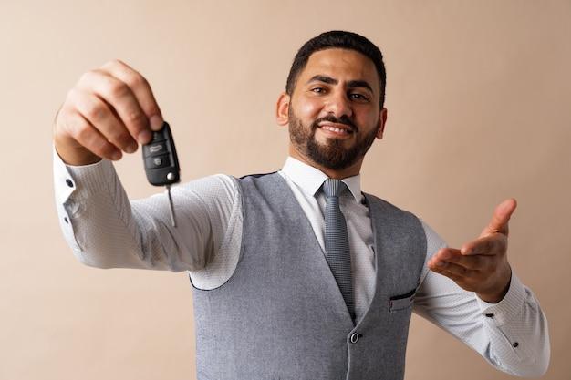 Młody arabski facet trzymający kluczyk do samochodu i pokazujący go na beżowym tle
