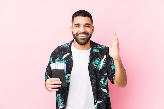 Młody arabski fajny mężczyzna trzyma kartę pokładową na białym tle, otrzymując miłą niespodziankę, podekscytowany i podnosząc ręce.