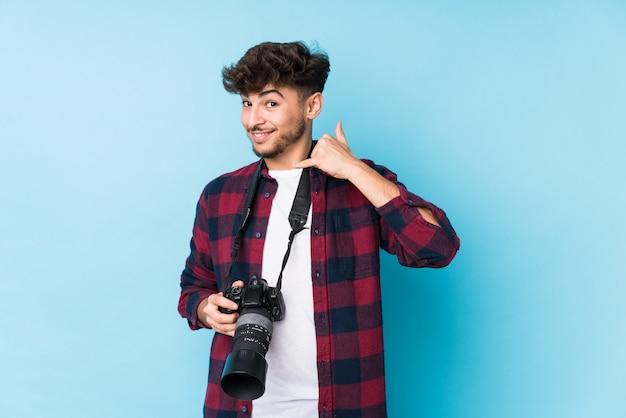 Młody arabski fotografa mężczyzna odizolowywał pokazywać telefonu komórkowego wezwania gest z palcami.