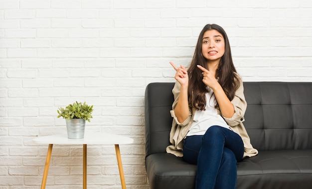 Młody arabski kobiety obsiadanie na kanapie zszokował wskazywać z palcami wskazującymi kopia.
