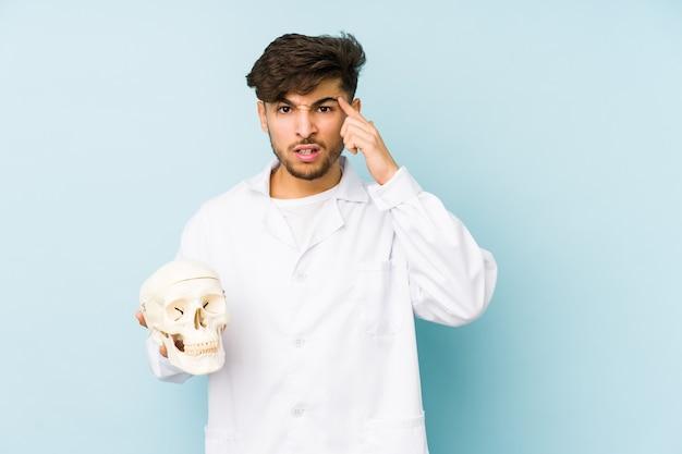 Młody arabski lekarz mężczyzna trzyma czaszkę pokazując gest rozczarowania palcem wskazującym.