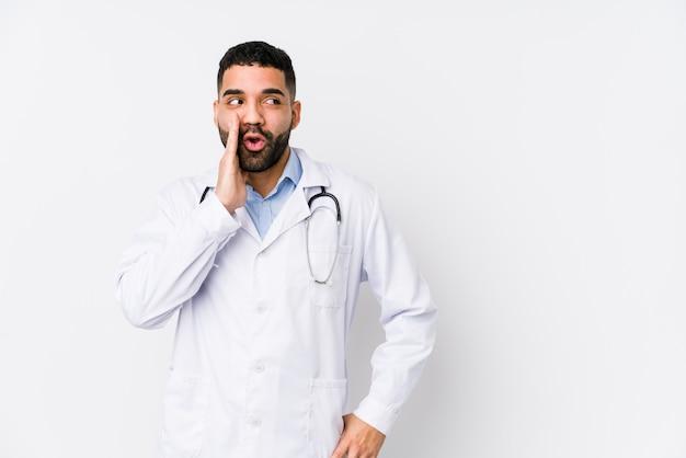 Młody arabski lekarz na białym tle mówi tajne gorące hamowanie wiadomości i patrzy na bok