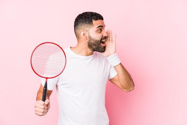Młody arabski mężczyzna bawić się badminton odizolowywał krzyczeć i trzymać palmowego pobliskiego rozpieczętowanego usta.