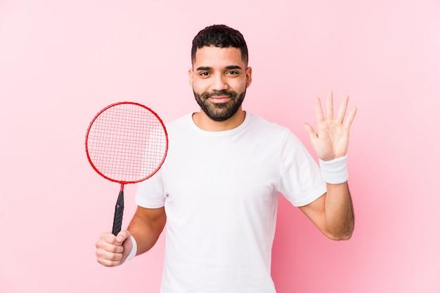 Młody arabski mężczyzna bawić się badminton odizolowywał uśmiechniętego rozochoconego seans liczbę pięć z palcami.