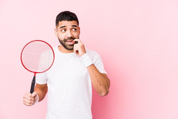 Młody arabski mężczyzna bawić się badminton odizolowywał zrelaksowanego główkowanie o coś patrzeje odbitkową przestrzeń.