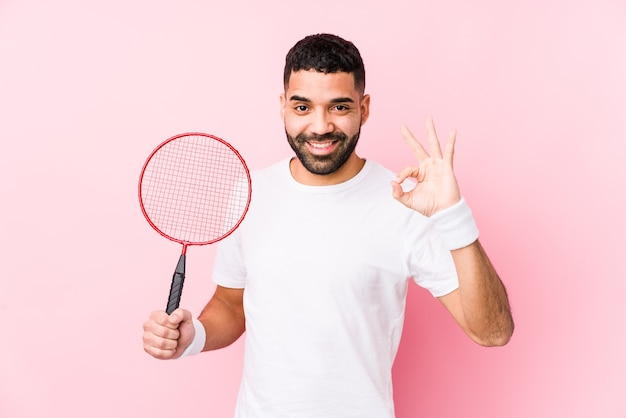 Młody arabski mężczyzna gra w badmintona na białym tle wesoły i pewny siebie, pokazując ok gest.