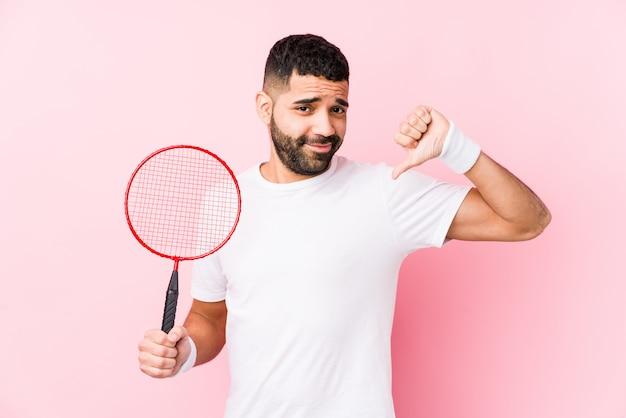Młody arabski mężczyzna grający w badmintona na białym tle czuje się dumny i pewny siebie, przykład do naśladowania.