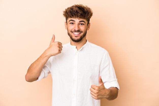 Młody arabski mężczyzna na białym tle na beżowym tle podnosząc oba kciuki do góry, uśmiechnięty i pewny siebie.