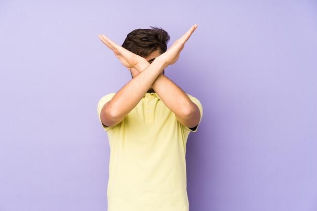 Młody arabski mężczyzna na białym tle na fioletowej ścianie, trzymając dwa skrzyżowane ręce, koncepcja odmowy.