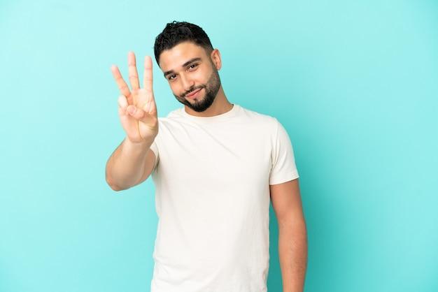 Młody arabski mężczyzna na białym tle na niebieskim tle szczęśliwy i liczący trzy palcami