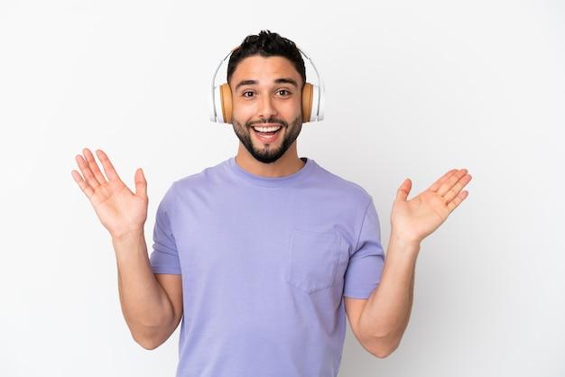 Młody arabski mężczyzna na białym tle zaskoczony i słuchający muzyki
