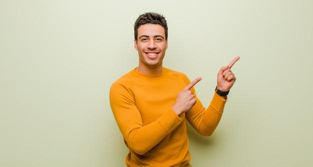 Młody arabski mężczyzna ono uśmiecha się szczęśliwie i wskazuje popierać kogoś i upwards z oba rękami pokazuje przedmiot w kopii przestrzeni przeciw płaskiej ścianie