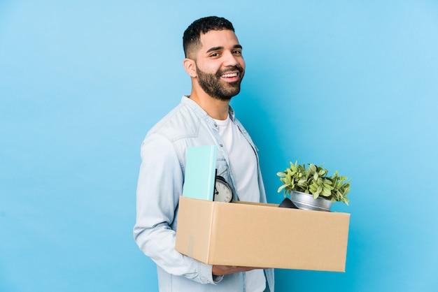 Młody arabski mężczyzna przeprowadzający się do nowego domu na białym tle wygląda na uśmiechniętego, wesołego i przyjemnego.