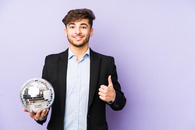 Młody arabski mężczyzna trzyma partyjną piłkę uśmiecha się kciuk up i podnosi