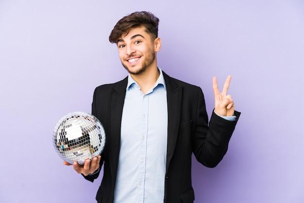 Młody arabski mężczyzna trzyma piłkę imprezową na białym tle radosny i beztroski pokazując palcami symbol pokoju.