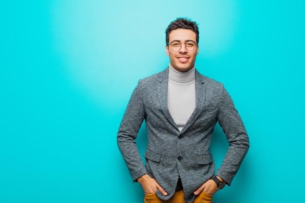 Młody arabski mężczyzna uśmiecha się radośnie i od niechcenia z pozytywnym, szczęśliwym, pewnym siebie i zrelaksowanym wyrazem twarzy na niebieskiej ścianie