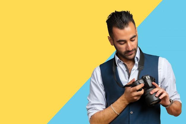 Młody arabski mężczyzna używa trzymający jego kamerę przygotowywającą strzelać, odizolowywającą