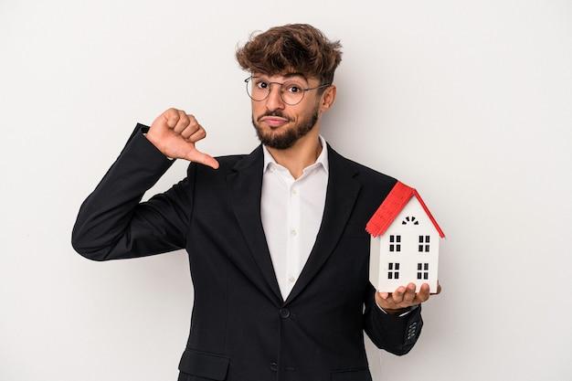 Młody arabski mężczyzna z branży nieruchomości, trzymający modelowy dom na białym tle, czuje się dumny i pewny siebie, przykład do naśladowania.