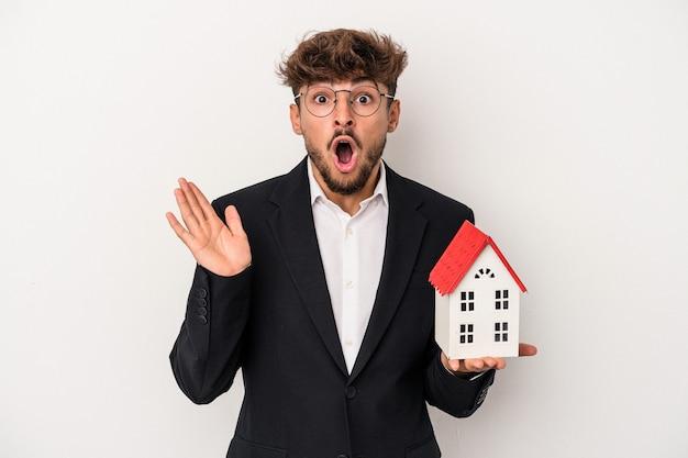 Młody arabski nieruchomości mężczyzna trzyma dom wzorcowy na białym tle na białym tle zaskoczony i zszokowany.
