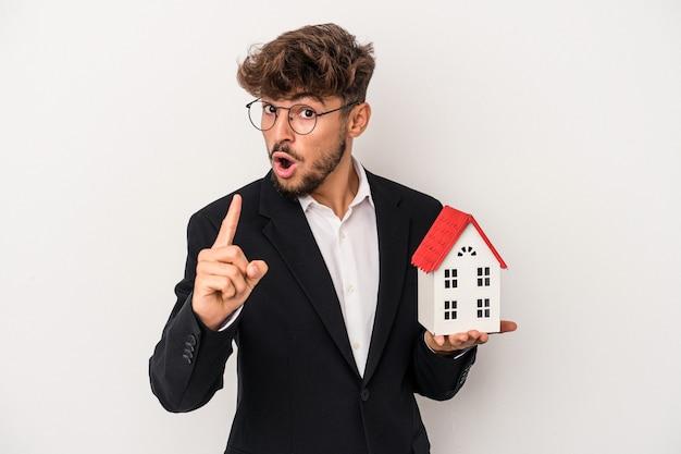 Młody arabski nieruchomości mężczyzna trzyma model domu na białym tle na białym tle mając pomysł, koncepcję inspiracji.