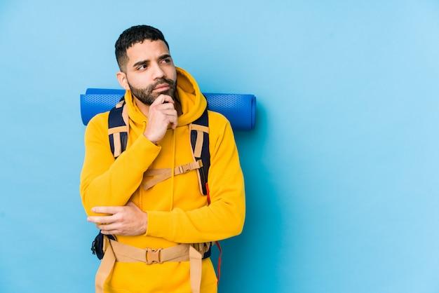 Młody arabski podróżnik backpacker mężczyzna na białym tle patrząc z ukosa z wyrazem wątpliwości i sceptyczny.