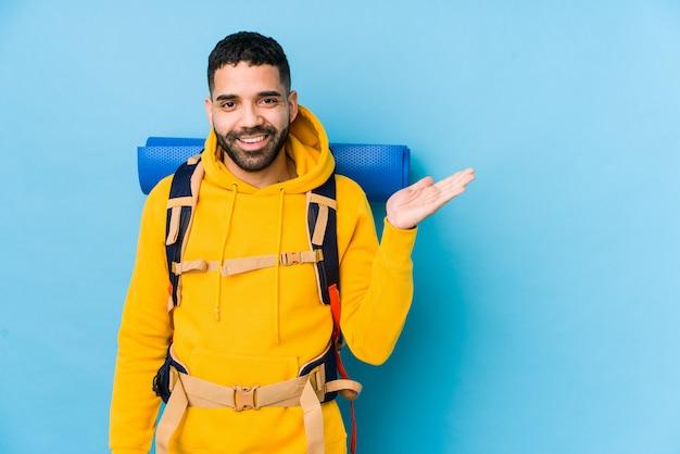 Młody arabski podróżnika backpacker mężczyzna odizolowywał pokazywać odbitkową przestrzeń na dłoni i trzymać inną rękę w talii.