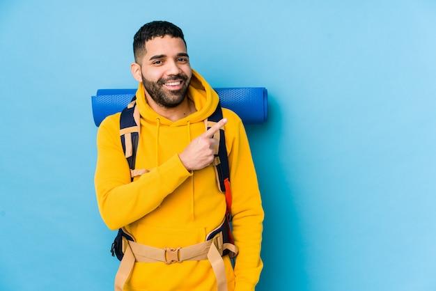 Młody arabski podróżnika backpacker mężczyzna odizolowywał uśmiecha się i wskazuje na boku, pokazuje coś przy pustą przestrzenią.