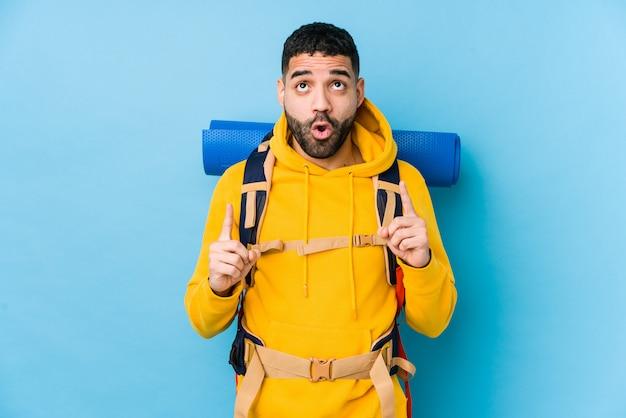 Młody arabski podróżnika backpacker mężczyzna odizolowywał wskazywać do góry z rozpieczętowanym usta.
