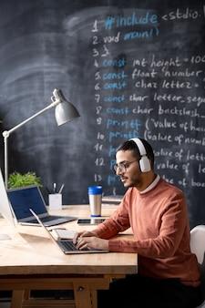 Młody arabski programista skupił się na kodzie internetowym siedząc przy drewnianym stole i pisząc na laptopie podczas słuchania dźwięku w słuchawkach