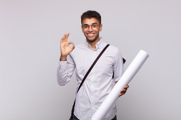 Młody architekt czuje się szczęśliwy, zrelaksowany i usatysfakcjonowany, okazując aprobatę w porządku gestem, uśmiechając się