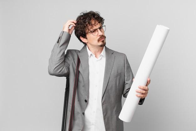 Młody architekt czuje się zdezorientowany i zdezorientowany, drapiąc się po głowie