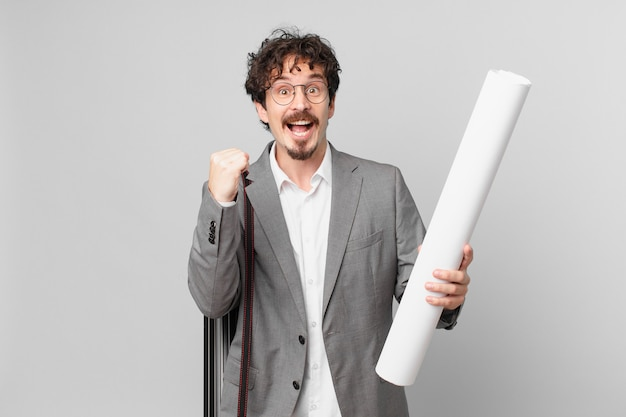 Młody architekt czuje się zszokowany, śmieje się i świętuje sukces