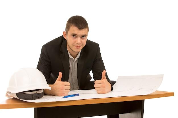 Młody architekt daje kciuki z sukcesu, gdy siedzi i pracuje nad projektem